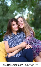Portrait of two smiling lovely young women of European appearance posing for photo shoot or advertising of cosmetics or clothing catalogs. Women's successful students came to park after school to