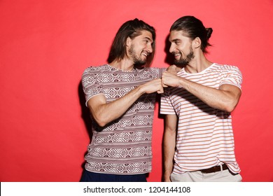 Portrait of two smiling twin brothers standing isolated over red background, giving fist bump