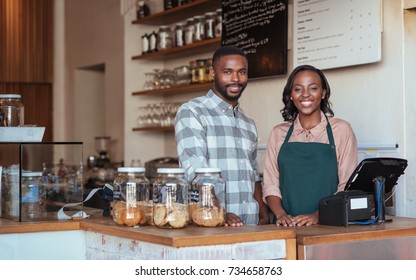Portrait of two smiling young African entrepreneurs standing welcomingly together behind the counter of their trendy cafe