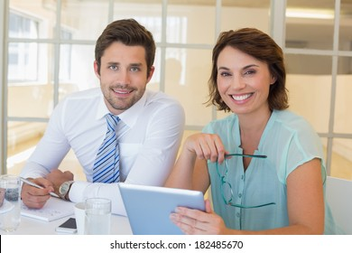 Portrait of two smiling young business people with digital tablet in the office