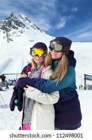Portrait of two smiling young girls in protective masks at a ski resort in the background of mountains and blue sky