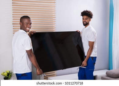 Portrait Of Two Smiling Young Male Movers Placing The Television In The Living Room
