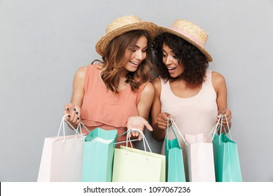 Portrait of two smiling young women dressed in summer clothes looking inside shopping bags isolated over gray background