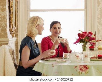 Portrait of two smiling young women having tea at dining table
