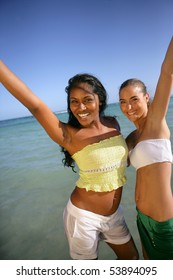 Portrait of two smiling young women in front of the sea