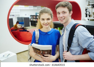 Portrait of two student, boy and girl, smiling looking at camera in library of modern college