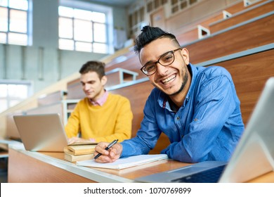 Portrait of two students sitting at desks in modern auditorium at college and preparing for class, focus on young Middle-Eastern man looking at camera and smiling, copy space