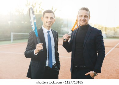 Portrait of two successful business man holding tennis rackets on shoulders while looking to camera smiling, dressed in suits on tennis court background. Success, partnership, friendship.
