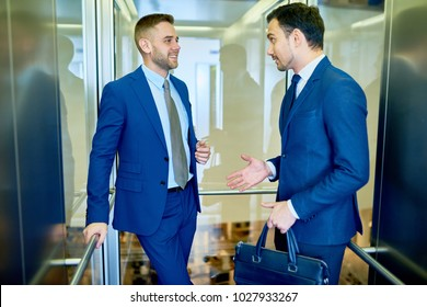 Portrait of two successful businessmen chatting cheerfully riding glass elevator in modern office building