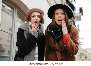 Portrait of two surprised girls dressed in autumn clothes walking on a city street