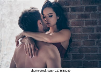 Portrait of two sweet gentle delicate gorgeous attractive fascinating lovable people married spouses kissing making love honey moon in hotel loft industrial interior room wall