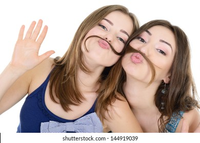 Portrait of a two teen girls have fun and make faces with moustache made of hair pigtail, isolated on white