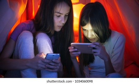 Portrait of two teen girls with smart phones under blanket at night - Shutterstock ID 1034060098