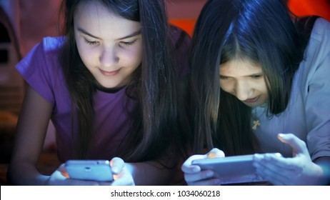 Portrait of two teenage girls with mobile phones at night - Shutterstock ID 1034060218