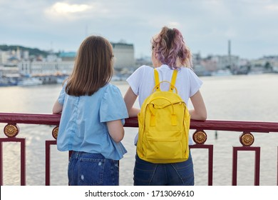 Portrait of two teenage girls standing with their backs on bridge over river, girls friends enjoying sunset on water surface, talking, relaxing. Friendship, lifestyle, youth, teens