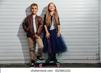 Portrait of two teenage school children on a garage door background in a city park street. girl is standing on pennyboard. Kids model friends, brown and black jackets, blue skirt, white T-shirt.