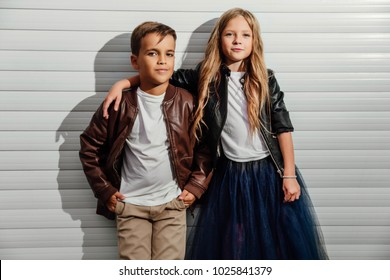 Portrait of two teenage school children on a garage door background in a city park street. Kids model friends, brown and black jackets, blue skirt, white T-shirt. Copy space for text message.