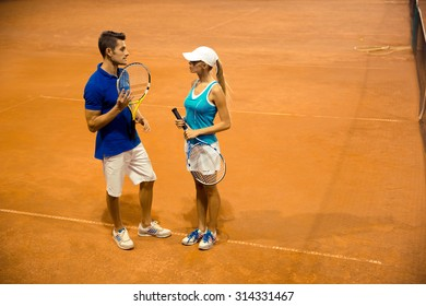 Portrait of a two tennis players with racket talking at court