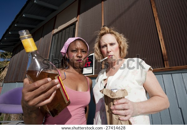 Portrait of two trashy drunk women outdoors