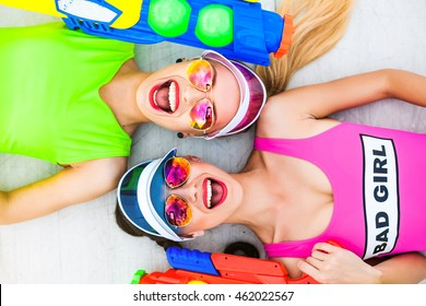 Portrait of two trendy cool hipster girls in bright lime and pink swimsuit holding colorful water pistols, guns, trendy hairstyles and makeup, sunglasses, laughing, summer, crazy emotions, top view