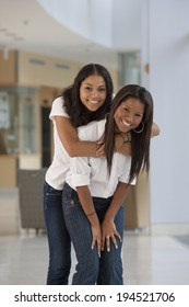 Portrait of two university students smiling and hugging