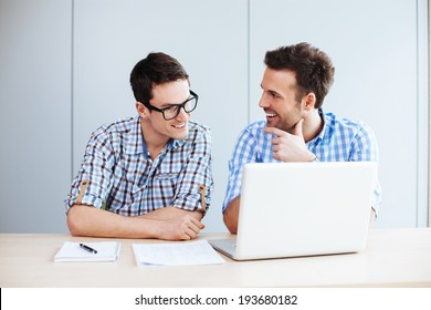 Portrait of two web designers discussing a project in front of a laptop