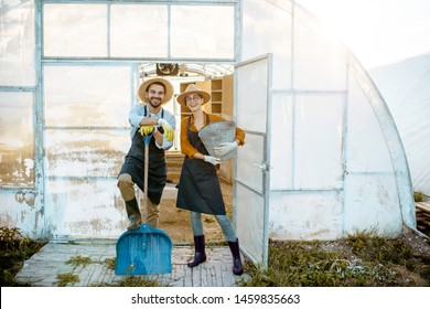 Portrait of a two well-dressed farmers or agronomists standing with working tools in front of the hothouse during the sunset