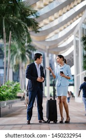 Portrait of two well-dressed and professional Asian businesspeople (a man and woman in a suit). They are standing next to one another in a modern and futuristic city during the day.