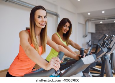 Portrait of two women doing cardio exercises at gym