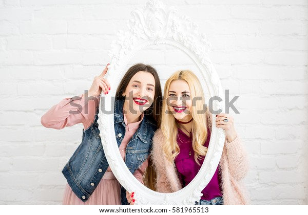 Portrait of two women friends in the frame on the white wall background