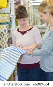 portrait of two women holding piece of fabric in store