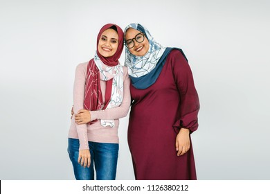 Portrait of two women partners standing next to one another. They are Muslim Malay women wearing tudung head scarves (hijab) and posing together for their photograph against a plain white background.