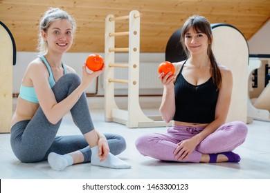 Portrait of two women pilates instructor showing orange balls for self-massage technique applying legs, back, neck and shoulder pain relief. Treatment pain concept. Practical use.