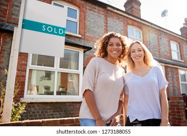 Portrait Of Two Women Standing Outside New Home With Sold Sign