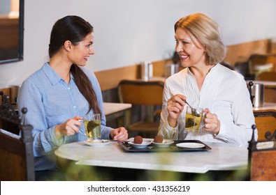 Portrait of two women with tea and chocolates in cafe