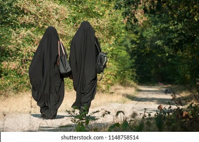 portrait of two women walking in the forest with black niqab on back view