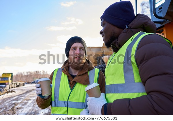 Portrait of two workers, one African-American, drinking coffee and chatting next to heavy industrial truck on worksite, copy space