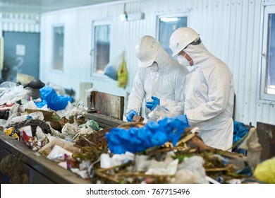 Portrait of two workers  wearing biohazard suits and hardhats working at waste processing plant sorting recyclable materials on conveyor belt