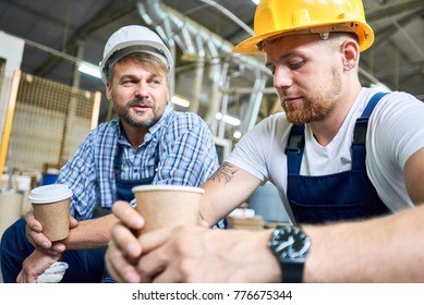Portrait of two workers wearing hard hats taking break from work drinking coffee and resting sitting on construction site