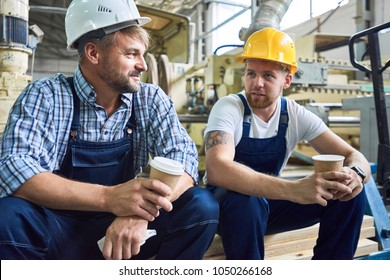 Portrait of two workers wearing hardhats taking break from work drinking coffee and resting sitting on pack of wood in workshop