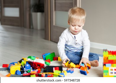 Portrait of two years old boy who is playing with colorful plastic bricks lego, sitting on the floor. Toddler having fun and building out of constructor bricks. Early learning. Development toys.