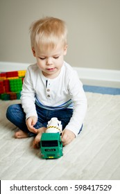Portrait of two years old boy who is playing with colorful plastic bricks and truck toy, sitting on the floor. Toddler having fun. Early learning. Development toys.