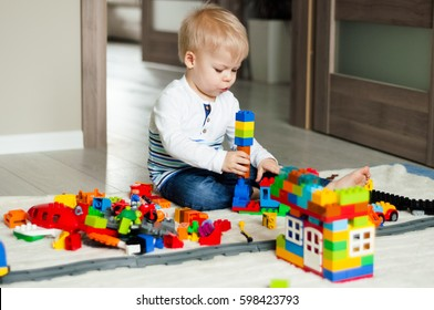 Portrait of two years old boy who is playing with colorful plastic bricks, sitting on the floor. Toddler having fun and building out of constructor bricks. Early learning. Development toys.