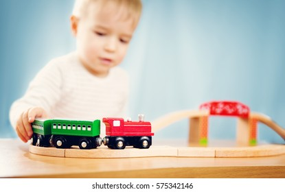 Portrait of a two years old child sitting at the table and playing with a railroad. Pretty little boy on blue background