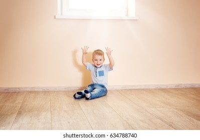 Portrait of a two years old child sitting on the floor. Pretty little boy at home