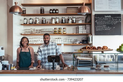 Portrait of two young African entrepreneurs standing welcomingly together behind the counter of their trendy cafe