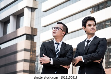Portrait of two young Asian businessmen in black suit standing with office building background