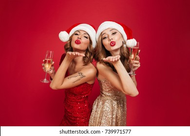 Portrait Of Two Young Attractive Girls In Christmas Hats And Dresses Holding Champagne Glasses And Sending