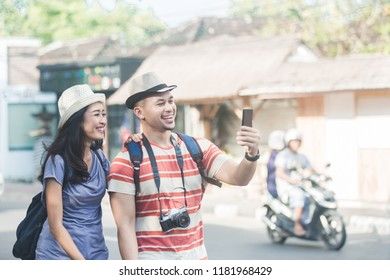portrait of two young backpackers taking selfies using mobilephones camera