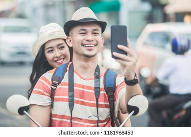 portrait of two young backpackers taking selfies using mobilephones camera while on motorbike